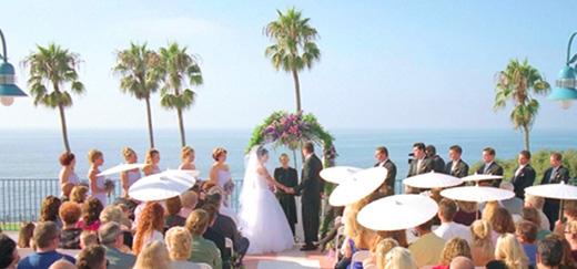Bride and groom holding hands during wedding ceremony at La Jolla Cove Suites.