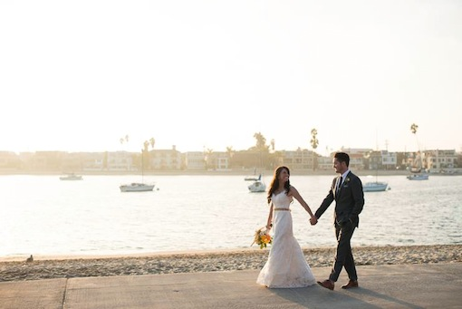 Bride and Groom holding hands on the sand at The Garty Pavilion.