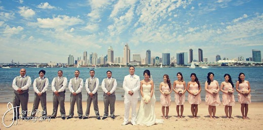 Events Inspired has the whole wedding party standing on a beach in front of a water view of downtown San Diego.