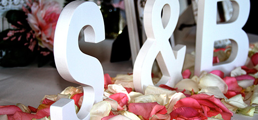 Letters forming the couples initials on a flower bed table. Read up on our tips and tricks to throw the perfect anniversary party.