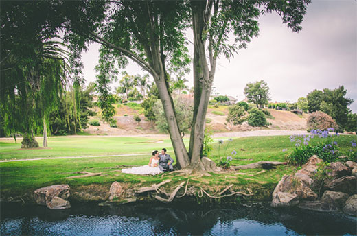 Newly married couple under a tree by the water at El Camino Country Club