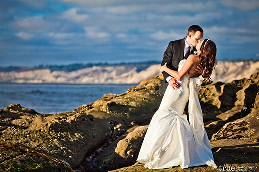 A bride and groom kissing on the rocks
