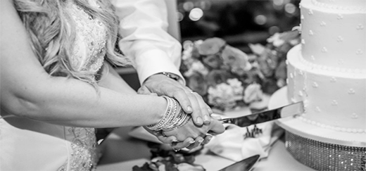 Couple's Hands Cutting Cake