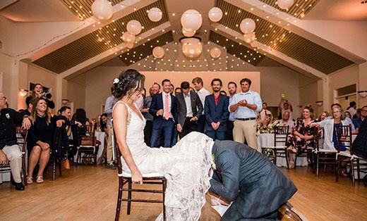 Groom Retrieving Garter From Bride
